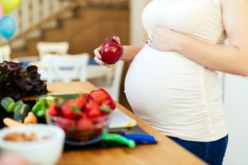 вагітна дівчина тримає яблуко