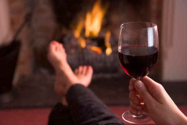 Келих вина в руці на тлі каміна