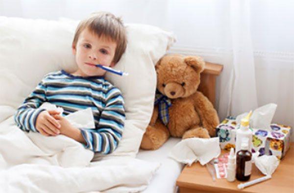 Хворий хлопчик в ліжку з градусником у роті