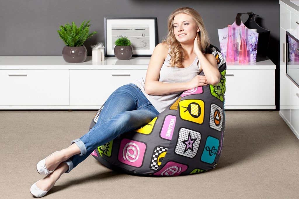Девушка наслаждается просмотром телевизора лежа в кресло-мешке