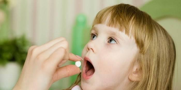 Дівчинка дають таблетку