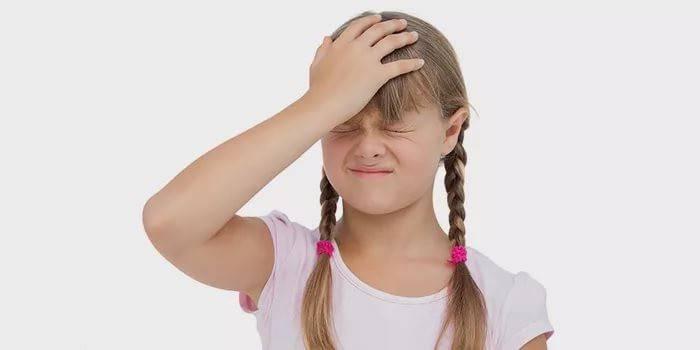 Дівчинка тримається рукою за лоб