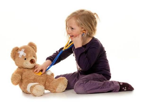 Дівчинка грає з медведесм