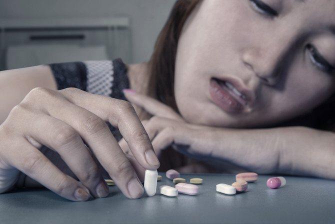 Дівчинка-підліток сидить за столом з жменю антідепресантів