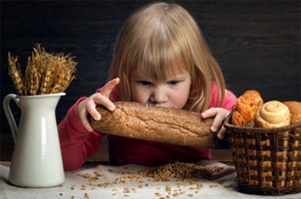 Дівчинка жадібно дивиться на пшеничний хліб, поруч булочки в кошику и Колос пшениці