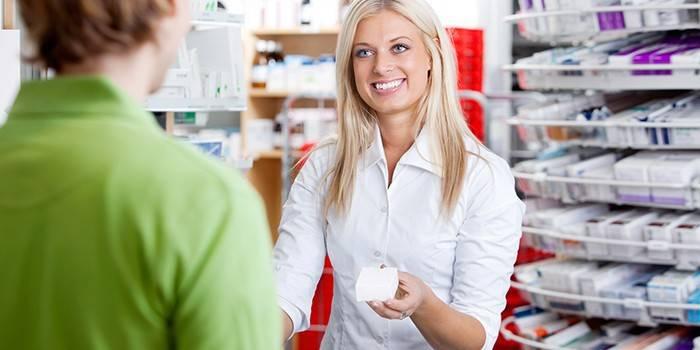 Дівчина аптекар консультує покупця