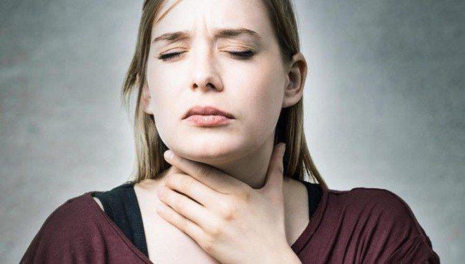 Дівчина тримає горло