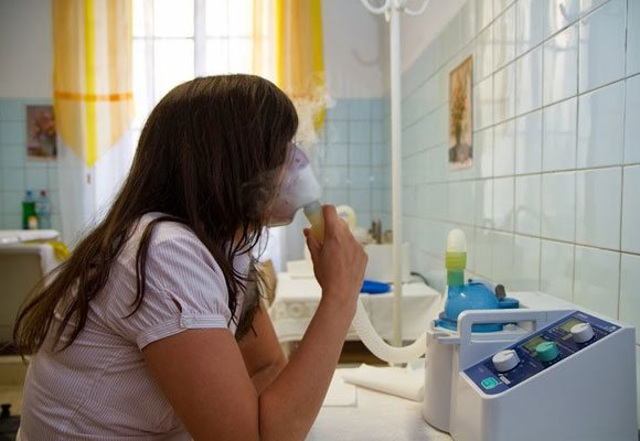 Дівчина дихає ліками з інгалятора