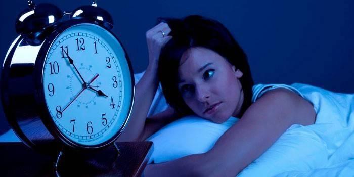 Дівчина лежить в ліжку і дивиться на годинник