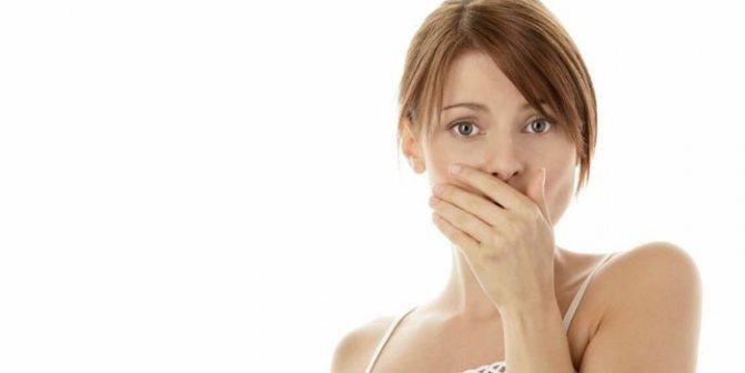 Дівчина прикриває рот рукою