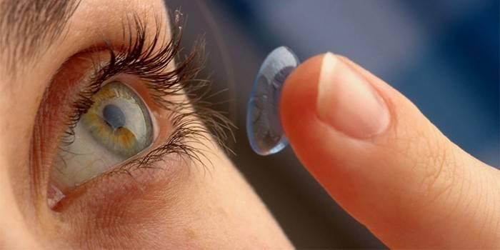 Дівчина з контактних лінзою на пальці