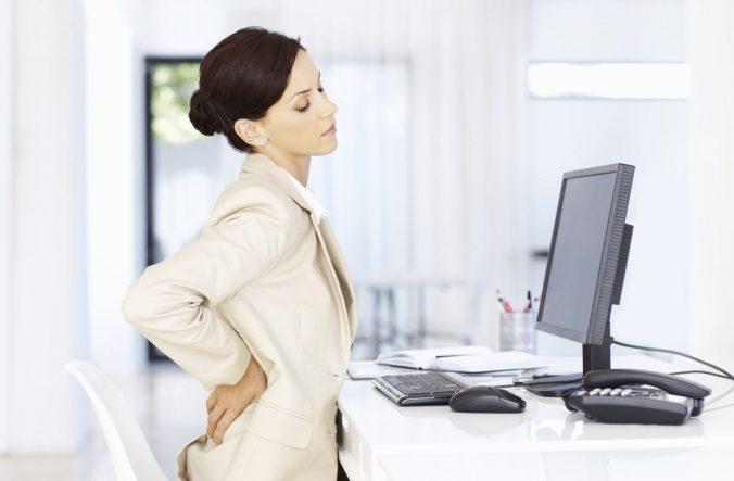 Дівчина за комп'ютером тримається за поперек