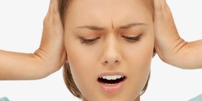 Дівчина закриває вуха руками