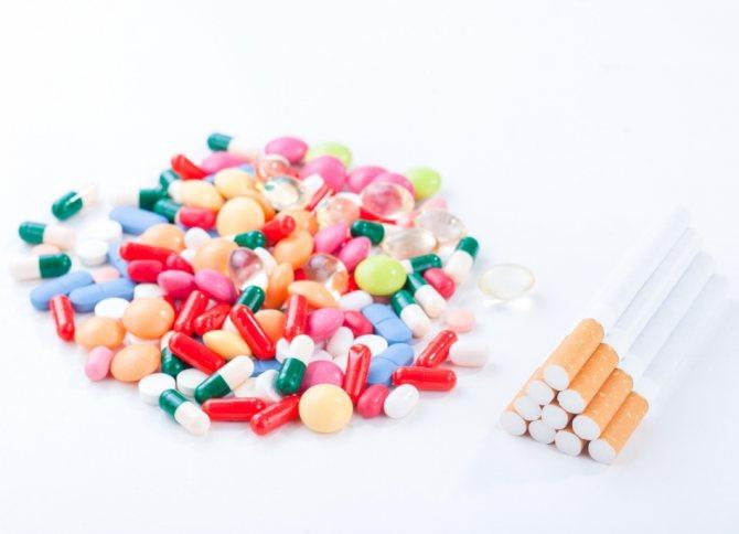 Гора різніх таблеток и капсул антідепресантів при відмові від куріння поруч зі стопкою сигарет
