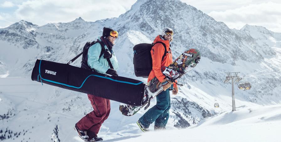 Парень и девушка идут кататься на лыжах в горы