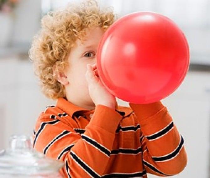 Хлопчик надуває кульку