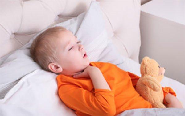 Хлопчик в ліжку кашляє і тримається за горло