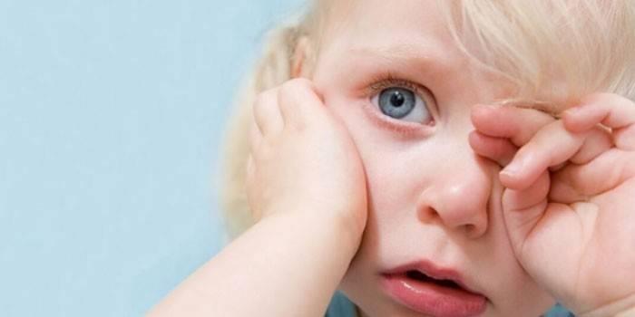 Маленька дівчинка тре око рукою