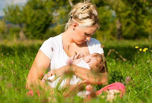Мама годує грудьми на сонці