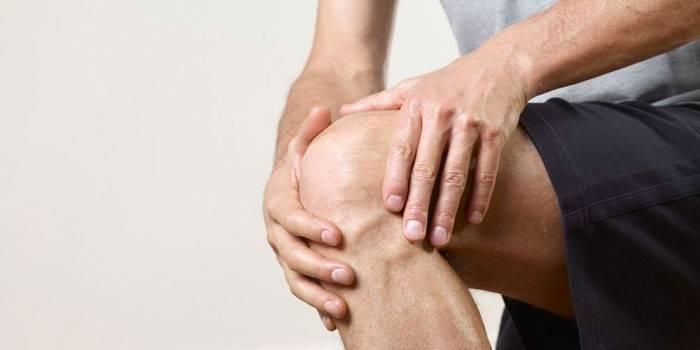 Чоловік трімає руки на коліні