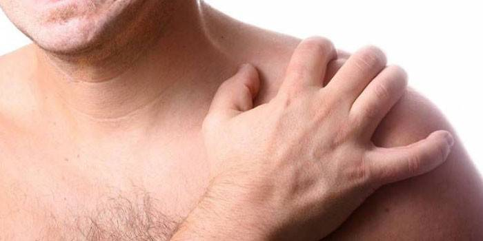 Чоловік тримається рукою за плече