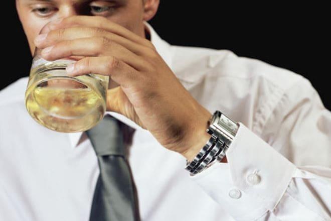 Чоловік п'є віскі