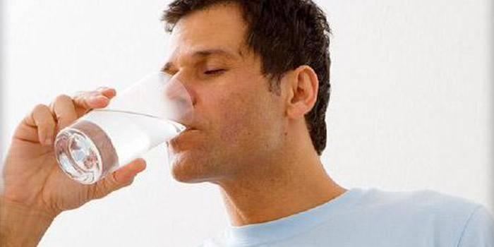 Чоловік п'є воду зі склянки