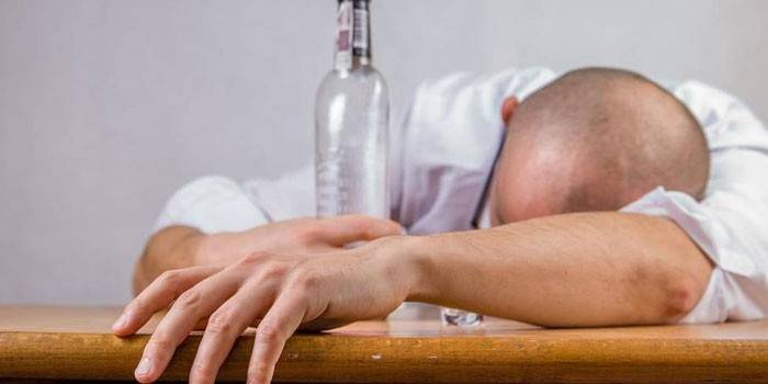 Чоловік з пляшкою на столі