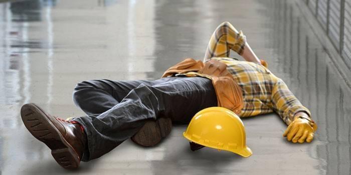 Чоловік в робочому одязі лежить без свідомості