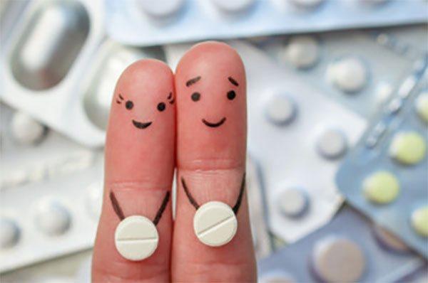 На задньому плане пластинки з таблетками.  На передньому - два пальці, на кожному по таблетці и намальовані мордочки