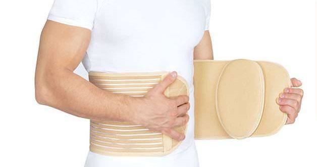 Пацієнт одягає бандаж на жівіт.