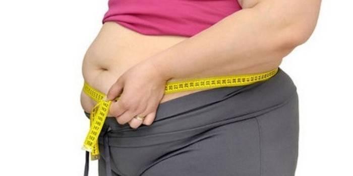 Повна жінка вимірює об'єм талії сантиметром
