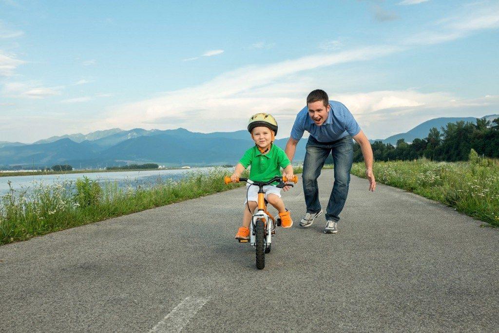 Папа учит ребенка кататься на велосипеде