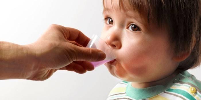 Дитині дають сироп з мірного стаканчика