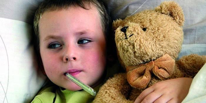Дитина з градусником у роті и з іграшковім Ведмідь в руці