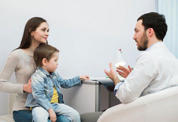 Дитина сидить у мами на руках. Доктор щось пояснює