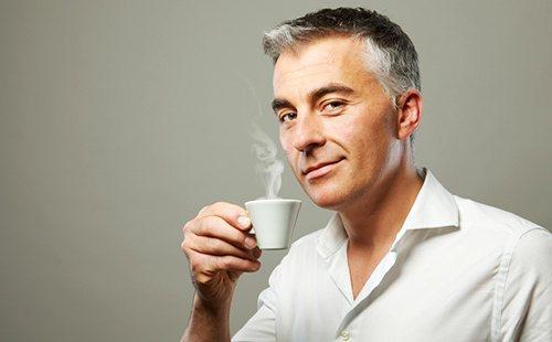 Сивуватий чоловік з багатозначною посмішкою тримає чашку