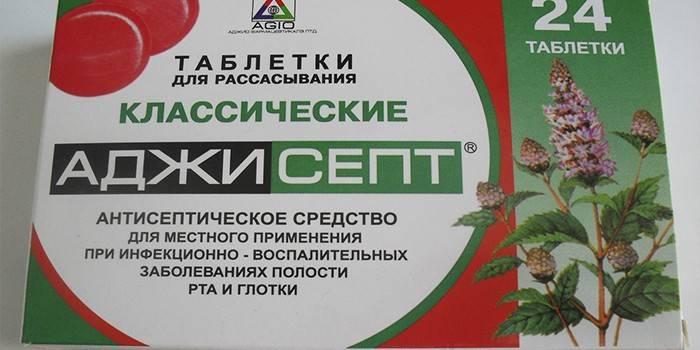 Таблетки для розсмоктування Аджісепт в упаковці