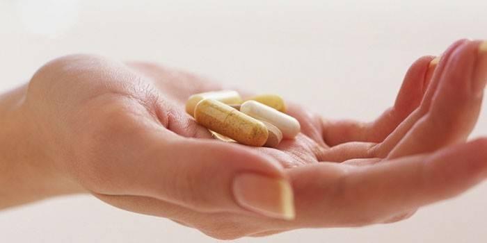 Таблетки і капсули на долоні