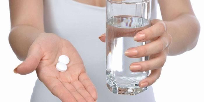 Таблетки і стакан води в руках у дівчини