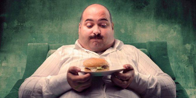 Огрядний чоловік з гамбургером