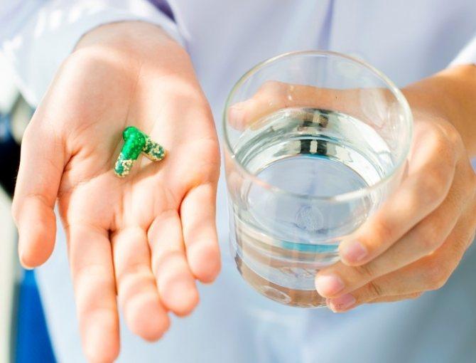 лікар тримає таблетку і стакан з водою