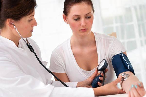 Лікар вимірює тиск пацієнтці