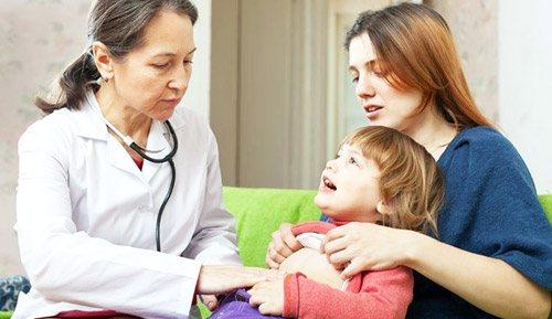 лікар оглядає хвору дитину