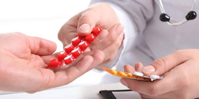 Лікар передає таблетки пацієнтові