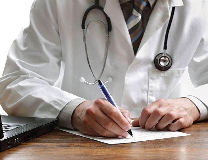 лікар підпісує папери