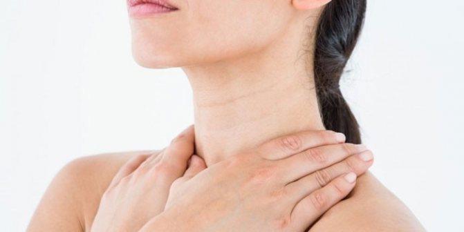 Жінка трімається за горло