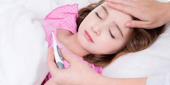 Жінка вімірює температуру у сплячої дівчинки