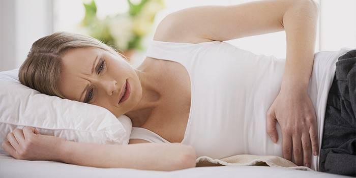 Жінка лежить і тримається за живіт