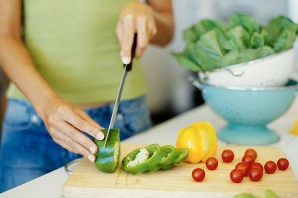 Жінка нарізає овочі